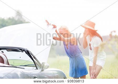 Friends examining broken down car on sunny day