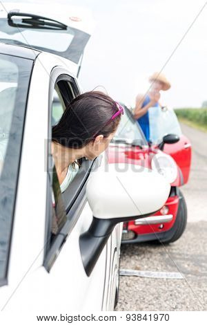 Woman looking at female crashing car on road
