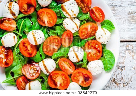 Salad Of Mozzarella, Cherry Tomatoes And Spinach With Balsamic Sauce Closeup