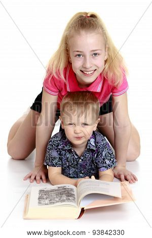 Big sister and little brother reading a book lying on the floor