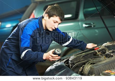 Car servicing, oil and filter replacing maintenace. Selective focus on mechanic face