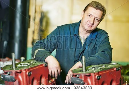 industrial worker assembler portrait with gearbox utits at manufacture workshop