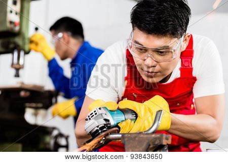 Two industrial workers in Asian metal factory with electrical grinding tool and power drill machine