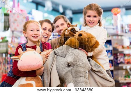 Family with stuffed elephant in toy store playing, girl sitting on plush toy