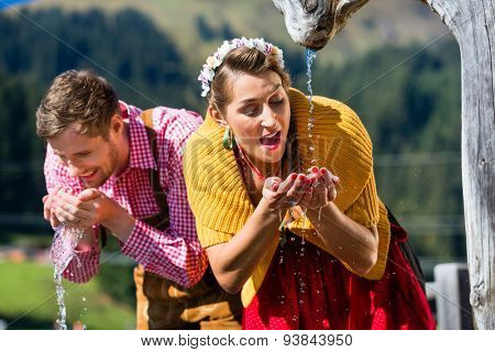 Couple in alp mountains drinking water from source, scene set with traditional clothing