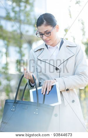 Businesswoman putting digital tablet in bag outdoors
