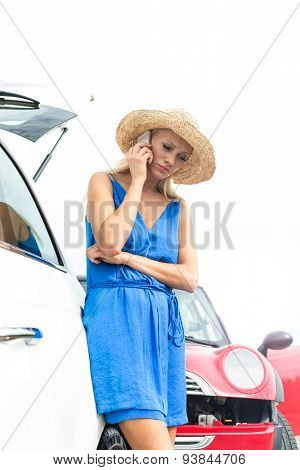 Low angle view of tensed woman using cell phone by broken down cars