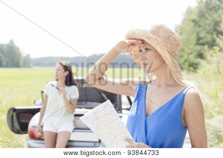 Young woman with map looking away while friend leaning on convertible in background