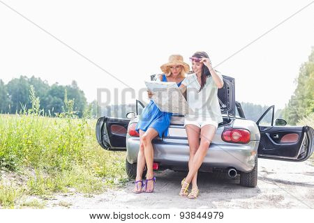 Female friends reading map while leaning on convertible