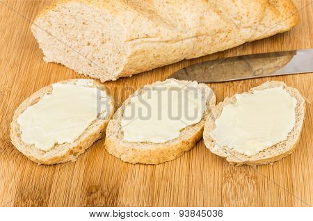 Three Sandwichs With Butter And Loaf Bread On Board
