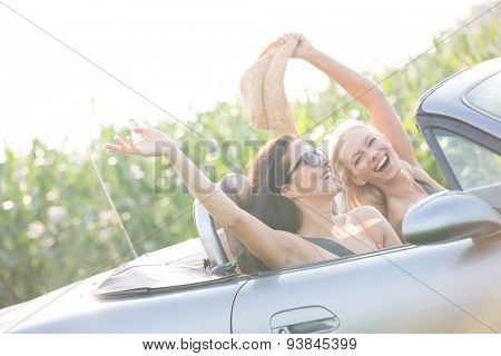 Excited female friends enjoying road trip in convertible on sunny day
