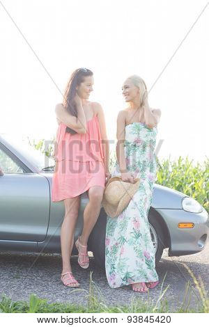 Happy female friends conversing while standing by convertible against clear sky