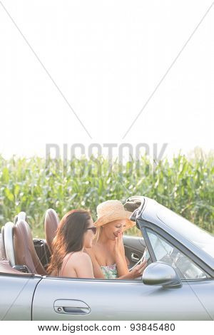 Female friends reading map in convertible against clear sky