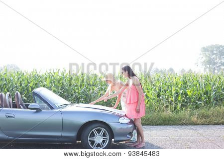 Female friends reading map on convertible against clear sky