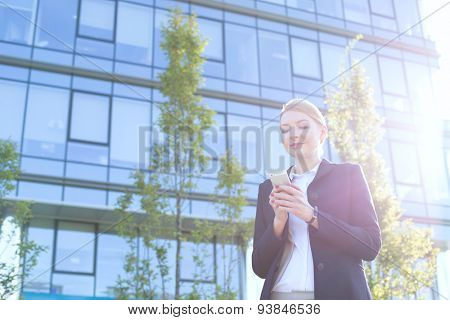 Businesswoman text messaging through cell phone on sunny day