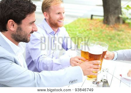 Businessmen toasting beer glasses with female colleague at outdoor restaurant