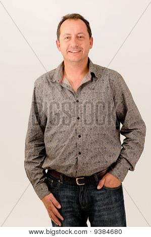 handsome male model standing with one hand in pocket of jean