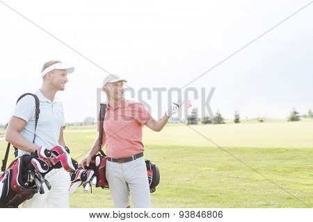 Man showing something to friend at golf course against clear sky