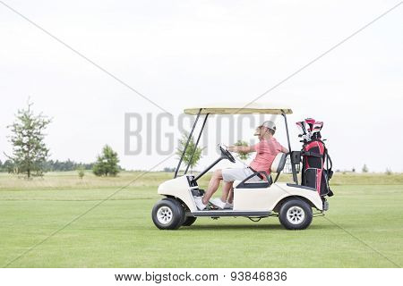 Side view of couple sitting in golf cart against clear sky