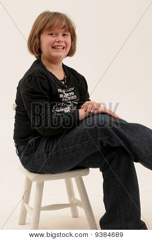 beautiful brown hair teenager smiling with dimple in cheek sitting on chair