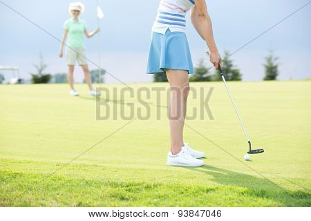 Low section of woman playing golf with female friend