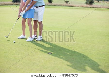 Low section of couple playing golf