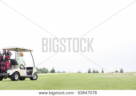 Couple sitting in golf cart against clear sky