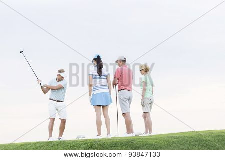 Group of friends looking at man playing golf against clear sky