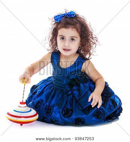 Dark-haired curly-haired little girl spinning dreidel sitting on