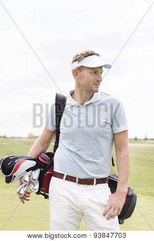 Thoughtful mid-adult man carrying golf club bag against clear sky