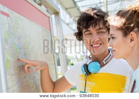 Happy man showing places on map to woman outdoors