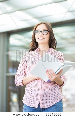 Thoughtful woman looking away while holding book outdoors