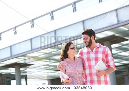 Happy couple looking at each other while walking in city
