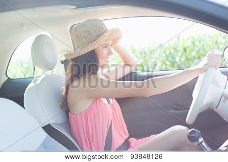 Side view of happy woman driving car
