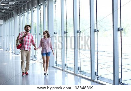 Full-length of couple holding hands while walking at covered passage