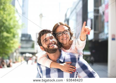 Cheerful woman pointing away while enjoying piggyback ride on man in city