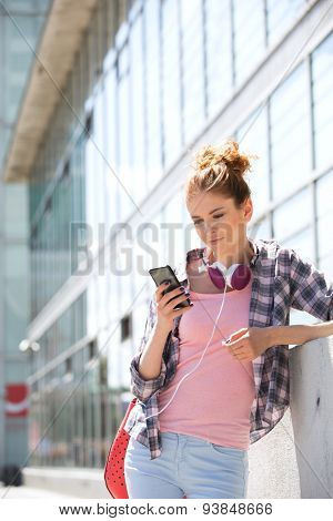 Young woman using smart phone outside office building