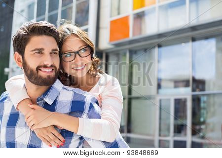 Loving man piggybacking woman in city