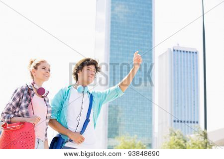 Happy woman standing with male friend hailing a taxi in city