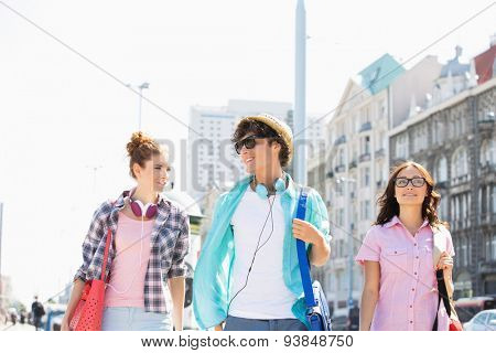 Happy friends talking while walking in city