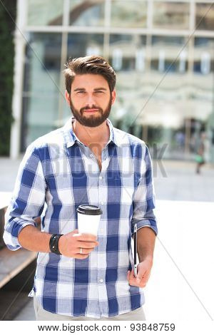 Portrait of confident man looking away while holding disposable cup and tablet PC in city