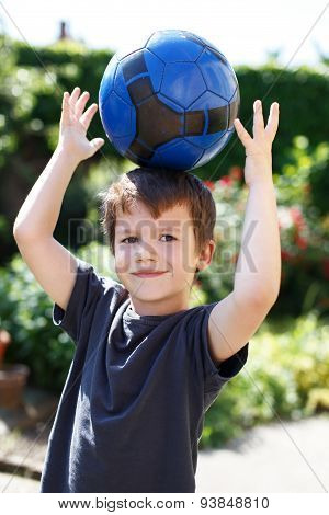 Little Boy With Soccer Ball On Head