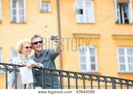 Happy middle-aged couple taking selfie through camera against building