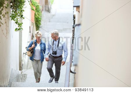High angle view of middle-aged couple holding hands while climbing steps outdoors