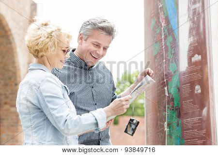 Cheerful middle-aged couple reading map in city
