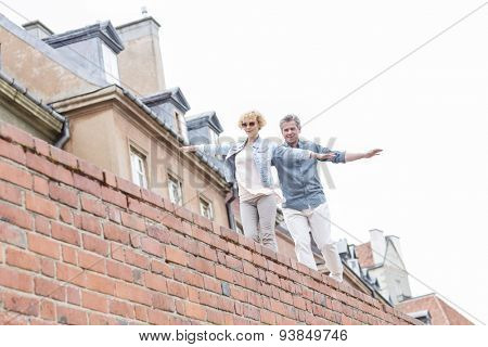 Low angle view of middle-aged couple with arms outstretched walking on brick wall against clear sky