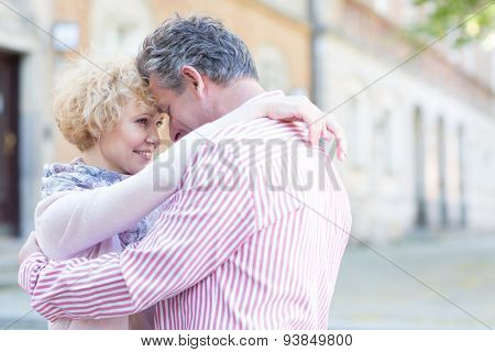 Happy middle-aged couple embracing in city