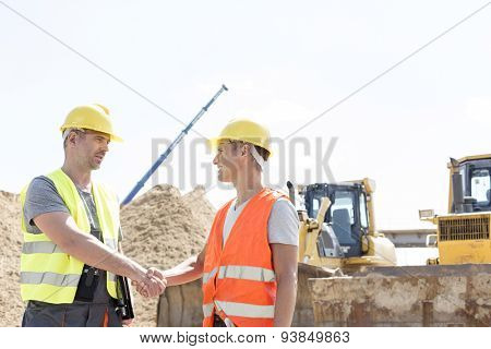 Architects shaking hands at construction site against clear sky