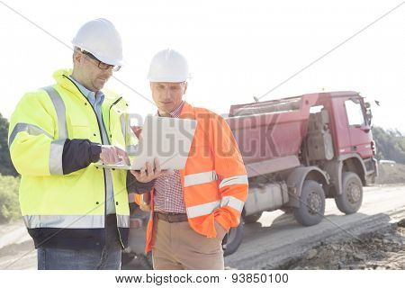 Engineers using laptop at construction site against clear sky on sunny day