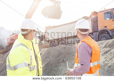 Engineer pointing at vehicles while discussing at construction site